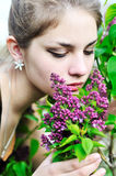 Flores de la lila de la muchacha que huelen adolescente Fotografía de archivo