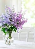 Flores de la lila del manojo en florero en la tabla fotos de archivo