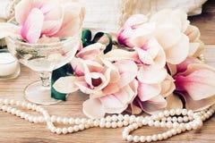 Flores de la magnolia con las perlas en la tabla de madera Imágenes de archivo libres de regalías
