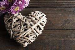 Flores de la margarita y corazón de mimbre decorativo Imagen de archivo