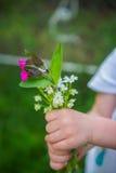 Flores de la primavera en manos del pequeño niño Imagen de archivo
