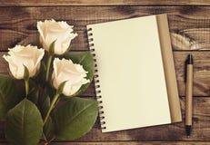 Flores de la rosa del blanco con el cuaderno y la pluma Fotografía de archivo