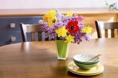 Flores de los tulipanes, del narciso y de la lila en un florero del vidrio verde en una tabla de madera Arreglo de la tabla fotografía de archivo libre de regalías