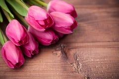 Flores de los tulipanes en la tabla de madera Foto de archivo