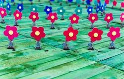Flores de madeira vermelhas e azuis em uma plataforma imagem de stock