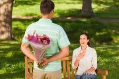 Flores de oferecimento do homem novo a sua esposa Imagens de Stock Royalty Free