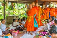 Flores de oferecimento dos povos budistas de segunda-feira às monges imagens de stock