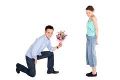 Flores de ofrecimiento del hombre ocasional a la mujer Foto de archivo libre de regalías