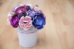 Flores de papel coloridas en un pequeño cubo blanco Fotografía de archivo