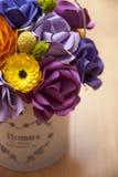 Flores de papel coloridas en un pequeño cubo blanco Imagen de archivo