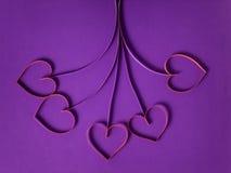 Flores de papel com corações no fundo roxo imagens de stock royalty free