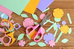 Flores de papel, hojas de papel, tijeras, pedazo de papel en una tabla de madera Fotografía de archivo libre de regalías