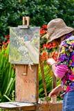 Flores de pintura de la mujer mayor en lona en jardín durante día soleado imagenes de archivo