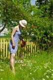 Flores de riego de la mujer joven en el jardín Imagen de archivo libre de regalías
