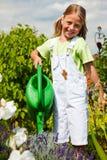 Flores de riego de la niña Imagen de archivo libre de regalías