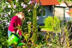 Flores de riego del niño feliz en el jardín Foto de archivo libre de regalías