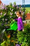 Flores de riego del niño feliz en el jardín Fotografía de archivo libre de regalías