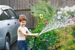 Flores de riego del niño pequeño de una manguera de jardín Imágenes de archivo libres de regalías