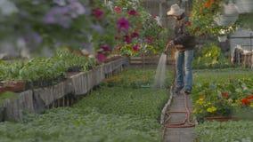 Flores de riego del trabajador adentro almacen de metraje de vídeo