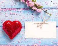 Flores de Sakura, coração vermelho decorativo e Empty tag na madeira azul Imagem de Stock