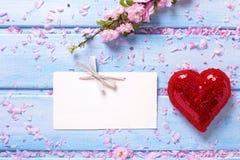 Flores de Sakura, coração vermelho decorativo e Empty tag na madeira azul Foto de Stock Royalty Free
