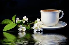 Flores de uma cereja e de um copo branco do café preto Imagem de Stock Royalty Free