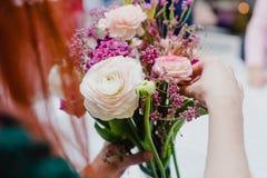 Flores decorativas en muchacha del jengibre de las manos imagen de archivo