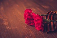 Flores del clavel y primer de George Ribbon en un fondo oscuro Día de la victoria - 9 de mayo Jubileo 70 años Fotos de archivo