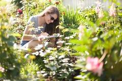 Flores del drenaje de la muchacha del estudiante en el parque Fotos de archivo libres de regalías