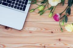 Flores del ordenador portátil y del eustoma en fondo de madera Imagenes de archivo