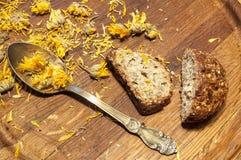 Flores del pan, de la cucharilla y de la maravilla en un tablero de madera. Foto de archivo libre de regalías