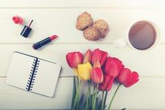 Flores del tulipán, café y otros artículos del ` s de las mujeres en los vagos de madera blancos Imagenes de archivo