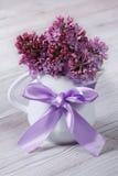Flores delicadas de la lila en un jarro blanco con un arco Fotografía de archivo