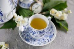 Flores delicadas florecientes del jazmín y una taza de té verde con un reloj mecánico en la cadena en el fondo Imágenes de archivo libres de regalías