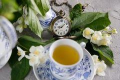Flores delicadas florecientes del jazmín y una taza de té verde tónico adornado con un reloj mecánico en una cadena Imagenes de archivo