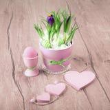 Flores do açafrão e decorações cor-de-rosa da Páscoa na madeira Imagens de Stock Royalty Free