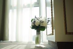 Flores do casamento para a noiva Mulher que guarda o suplente colorido do ramalhete perto da janela, no dia foto de stock royalty free