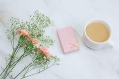 flores do cravo, caixa de presente cor-de-rosa, copo da bebida e e coração enchido do brinquedo em um espaço de mármore da cópia  fotografia de stock royalty free