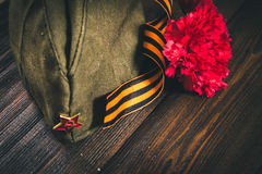 Flores do cravo, George Ribbon e tampão de guarnição militar com uma estrela vermelha 9 de maio Victory Day Fotografia de Stock Royalty Free
