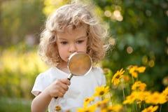 Flores do explorador da criança no jardim Fotografia de Stock Royalty Free