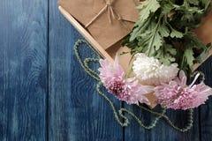 Flores do outono do crisântemo com grânulos e das letras em uma obscuridade - tabela azul com um lugar para a inscrição foto de stock royalty free