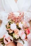Flores e bolinhos de amêndoa nas mãos da mulher imagens de stock