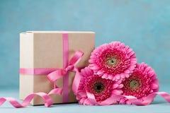 Flores e caixa de presente cor-de-rosa bonitas do gerbera com a fita na tabela de turquesa Cartão para o dia do aniversário, da m Imagem de Stock Royalty Free