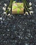 Flores e caixa de presente de Snowdrop no worktop esmeralda do granito da pérola Foto de Stock