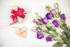 Flores e caixa roxas com um presente em um fundo branco Conceito comemorativo Imagens de Stock Royalty Free