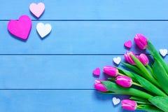 Flores e corações cor-de-rosa das tulipas na tabela de madeira azul para o 8 de março, o dia das mulheres internacionais, o anive Fotografia de Stock Royalty Free