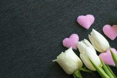 Flores e corações cor-de-rosa frescos das tulipas no fundo escuro com espaço da cópia Fotografia de Stock Royalty Free