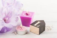 Flores e letra de madeira L na tabela branca Imagem de Stock