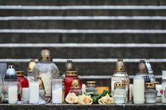 Flores e velas que comemoram a vítima de assassinato imagens de stock royalty free