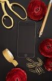 Flores elegantes rojas con los accesorios del teléfono y de la oficina en t negro Fotografía de archivo